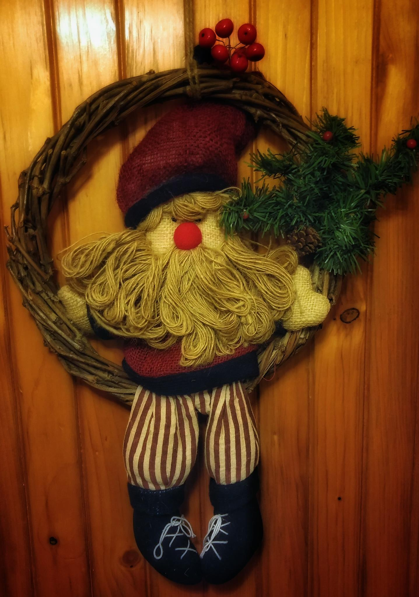 A crafty Santa wreath hangs on a wood wall